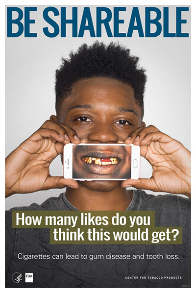 Poster portraying an African American teenage boy holding an iphone showing stained teeth as a health-related consequence of smoking cigarettes.