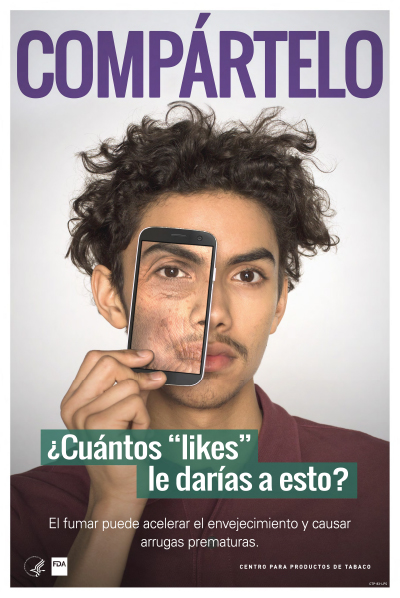 Spanish poster portraying a Hispanic teenage boy holding an iphone showing wrinkled skin as a health-related consequence of smoking cigarettes.