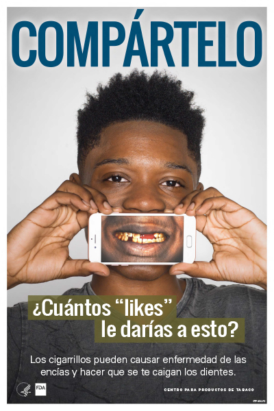 Spanish poster portraying an African American teenage boy holding an iphone showing stained teeth as a health-related consequence of smoking cigarettes.